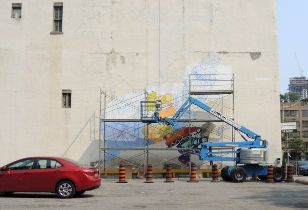 The beginnings of the mural on Court St. in Toronto.  The picture is drawn in blue on the wall, and the bottom part is painted.  Scaffolding is in place but no one is there at that moment.