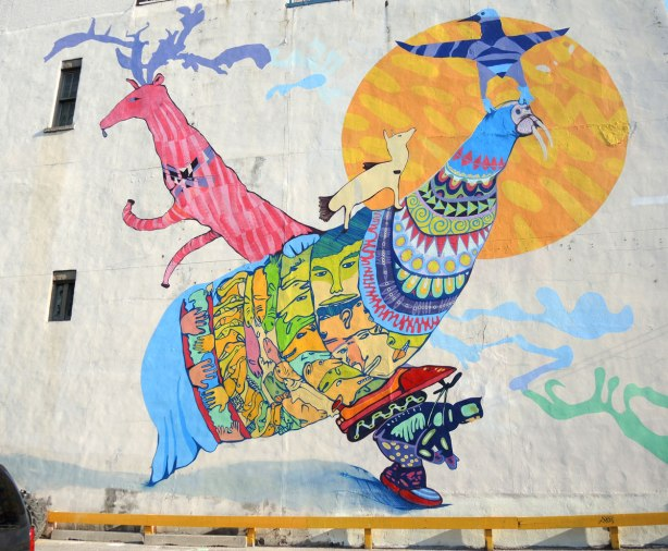 Completed mural of stylized and symbolic bird and snimal shapes in many bright colours.  It is at least two storeys high.