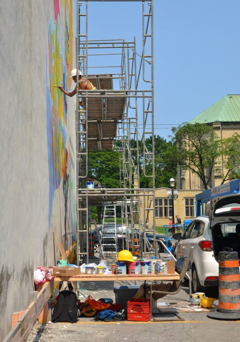 A man wearing a hard hat who is sitting on scaffolding and painting a mural on the side of a building.