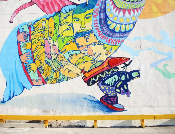 Close up picture of the mural's bottom center part showing a man in winter clothing with a snowmobile strapped to his back.  He is hunched over as he walks.  On the snowmobile of a very large bird shaped crature with faces covering its body.