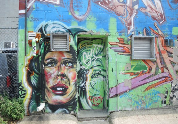 graffiti and street art in Graffiti Alley in Toronto - Back wall of a store, large woman's face on part of the wall
