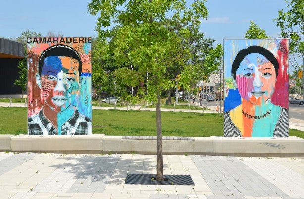 on a concrete plaza at the entrance to a park, large glass laminate artwork that is a colourful portrait of a person - two people, on the left is a young man with the word camaraderie and on the right is a young woman with the word appreciate