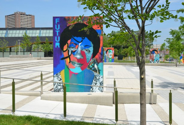on a concrete plaza at the entrance to a park, large glass laminate artwork that is a colourful portrait of a person - a young woman with the word future but spelled as f u t u r