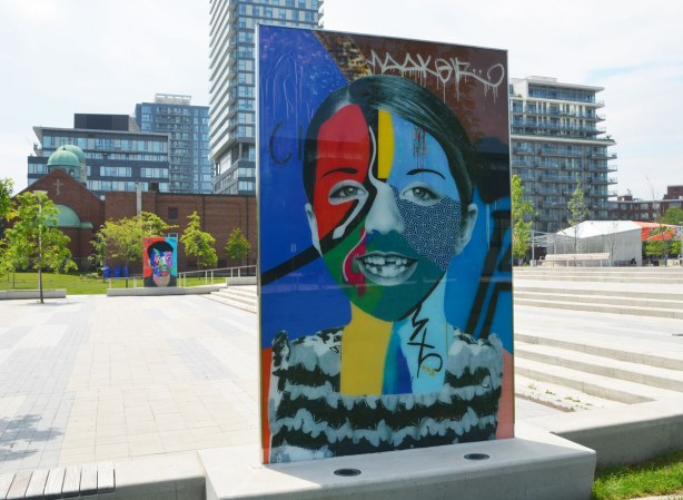 on a concrete plaza at the entrance to a park, large glass laminate artwork that is a colourful portrait of a person - a boy