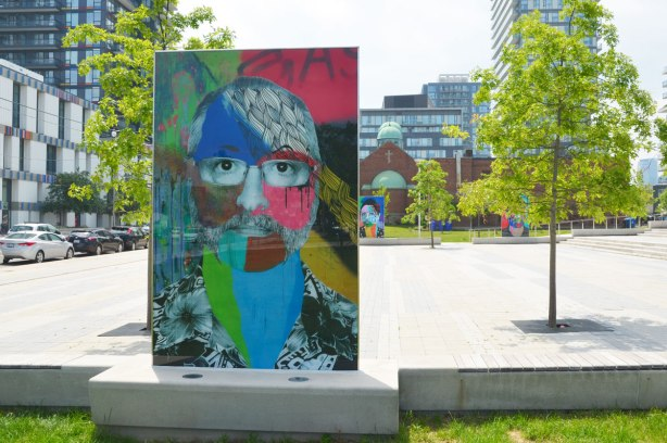 on a concrete plaza at the entrance to a park, large glass laminate artwork that is a colourful portrait of a person -
