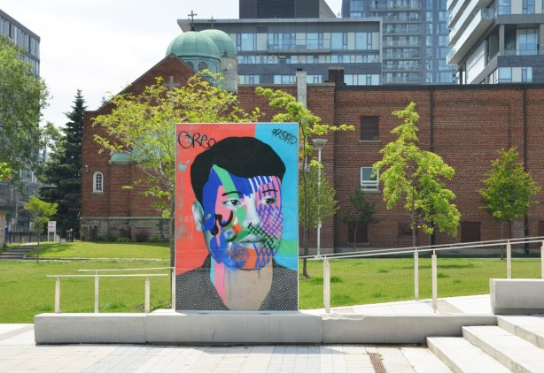 on a concrete plaza at the entrance to a park, large glass laminate artwork that is a colourful portrait of a person - a young man