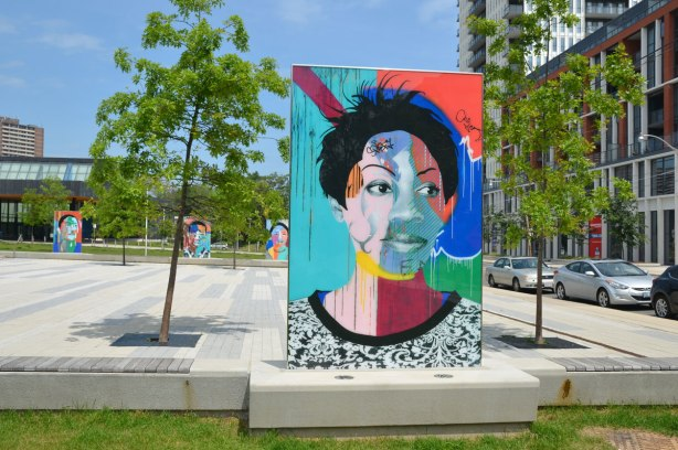 on a concrete plaza at the entrance to a park, large glass laminate artwork that is a colourful portrait of a person - a woman