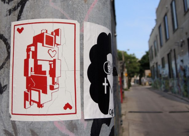 graffiti and street art in Graffiti Alley in Toronto - a lovebot of hearts playing card sticker on a metal pole beside a sticker of a woman's head with curly black hair and big earrings in the shape of a cross