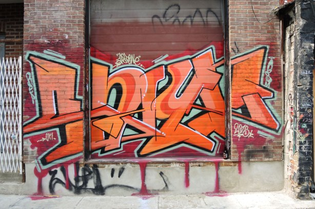 graffiti and street art in Graffiti Alley in Toronto - an orange tag on rusty red background, painted across a wide doorway