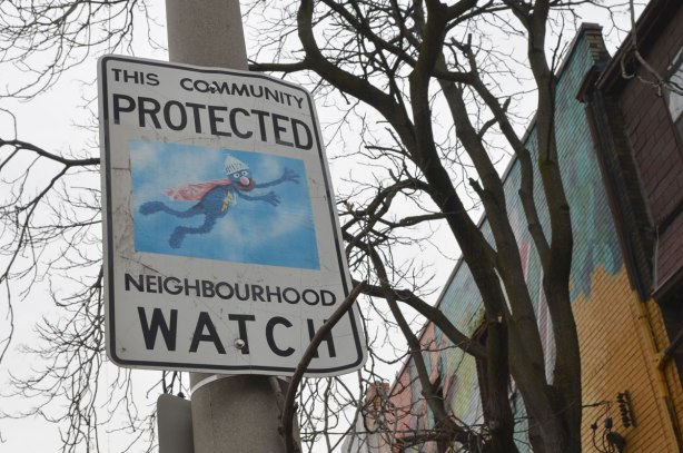 altered Neighbourhood Watch sign, Grover from Sesame Street in a superhero costume flying through the sky