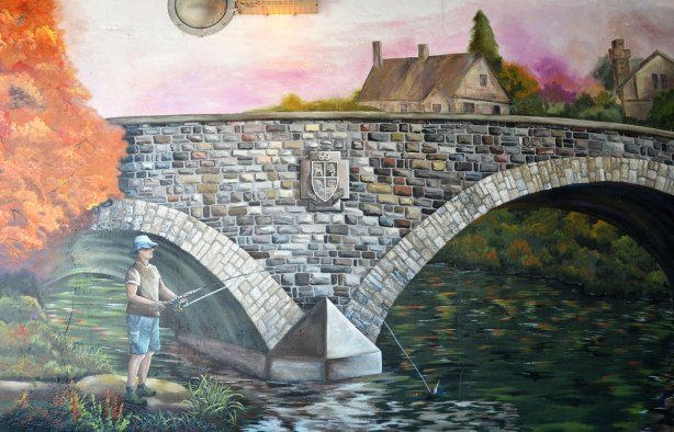 part of a mural showing a stone bridge over a river, the Humber River.  A man is fishing in the river from the shore.
