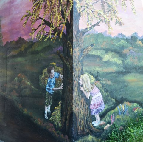 part of an historical mural on an underpass, two kids are playing, one on either side of a large tree that has been painted on the corner.