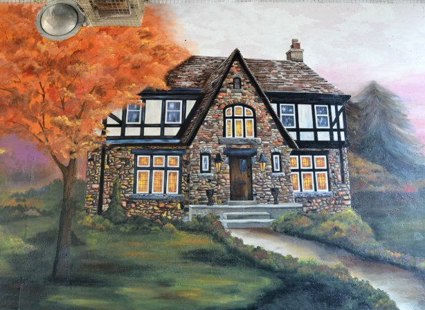 part of a mural showing a two storey stone house with fake tudor upper storey, in autumn, with tree with orange leaves beside the house.