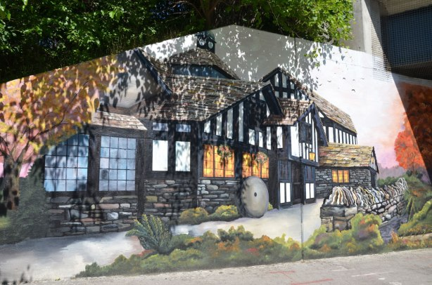 part of a mural that shows the Old Mill hotel, a tudor style two storey building with the lower part being made of stone