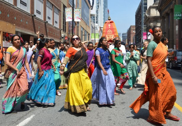 Some women in saris and men in traditional Indian clothes, dance and walk in a parade down Yonge St. as part of the Festival of India
