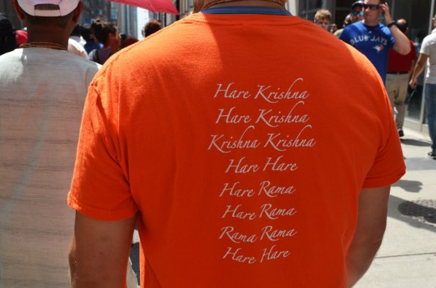 The back of a T shirt that a man is wearing.  It has all the words of the hare Krishna mantra on it.