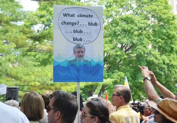 A group of people at a protest rally.  Somone is holding up a sign with a picture of Stephen Harper neck deep in water with the words, 'What climate change blub blub blub'