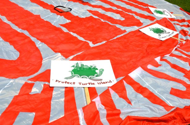A large parachute shaped piece of fabric in bright orange and white lies flat on the ground.  In it are three signs waiting for people to begin marching in the jobs, justice and climate change march.  The signs say 'Protect Turtle Island'