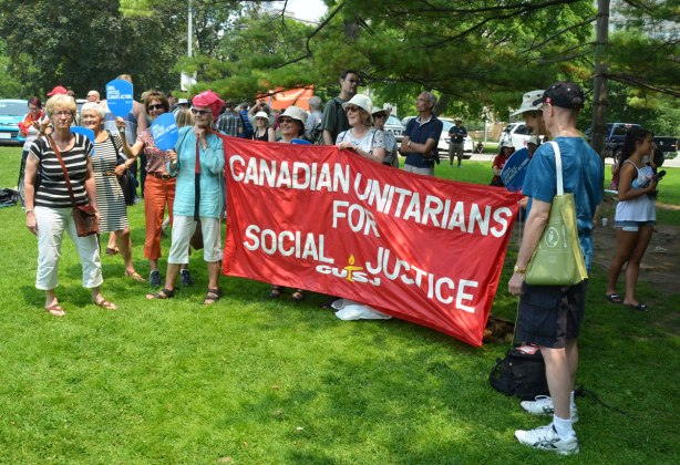A group of people holding a large red banner that says 'Canadian Unitarians for social justice'