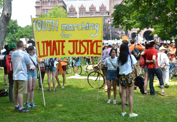 a groupd of young people standing beside a large yellow banner that says 'Youth marching for Climate Justice' at a protest rally in front of the Ontario parliament buildings.