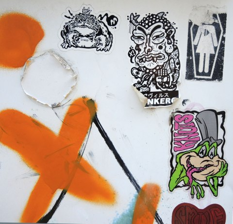 graffiti and street art in Graffiti Alley in Toronto - five stickers on white, also a big orange X.  One sticker is a knuts frog with its tongue stuck out.