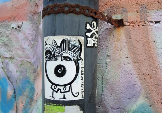 graffiti and street art in Graffiti Alley in Toronto - two stickers on a pole.  A small skull and cross bones and a large one that is a black and white creature with website liarliar.etsy.com on it.