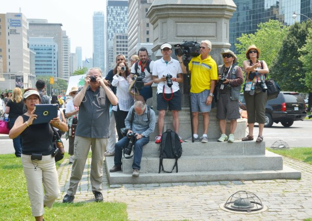 Many photographers are standing on the base of a statue while they wait for a protest march to begin in Toronto at Queens Park