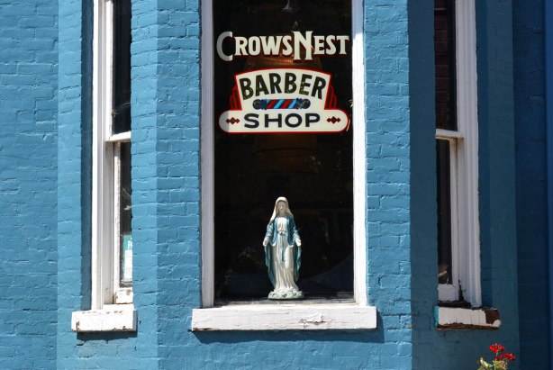 A figurine of the Virgin Mary with her light blue shawl stands piously in the window of a barber shop. The building is painted a light blue colour.