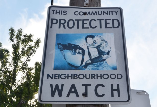 Neighbourhood watch sign with picture of Sigourney Weaver as Ellen Ripley in 'Aliens, carrying a child and a very big gun