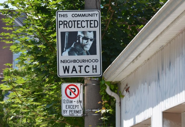 An altered Neighbourhood Watch sign. A picture of a black man wearing sunglasses and with a machine gun on his back
