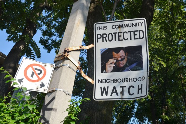 An altered Neighbourhood Watch sign. A picture of a man looking over the top of his sunglasses has been added to the sign.