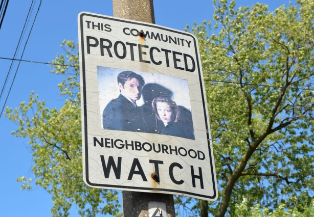 An altered Neighbourhood Watch sign. A man and a woman, agents Mulder and Scully from the TV series X Files