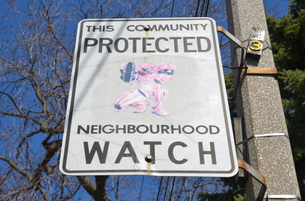 An altered Neighbourhood Watch sign. A picture of a superhero dressed head to toe in pink (or is it faded rad?) and holding a large weapon has been added to the sign