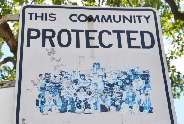An altered Neighbourhood Watch sign. A faded picture of a large group of transformers, the superheros from the old TV series.