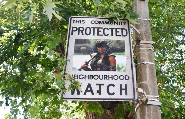 An altered Neighbourhood Watch sign. A woman. Xena the warrior princess character.