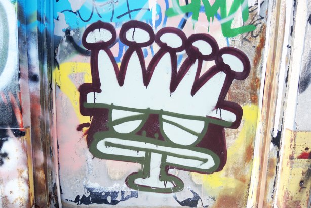 graffiti and street art in Graffiti Alley in Toronto - A basquiat crown on a cartoonish face on a door