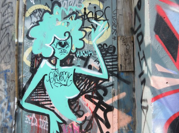 graffiti and street art in Graffiti Alley in Toronto - a sylized blue woman from the waist up.  Puffy curly hair.  She's been scribbled on including a heart on her chest.