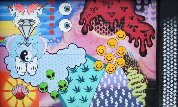 graffiti and street art in Graffiti Alley in Toronto - a collage like piece of street art on a garage door by clowntearz.  Googley eys, cannabis leaves, happy faces, zigzags, green  alien faces, red ooze