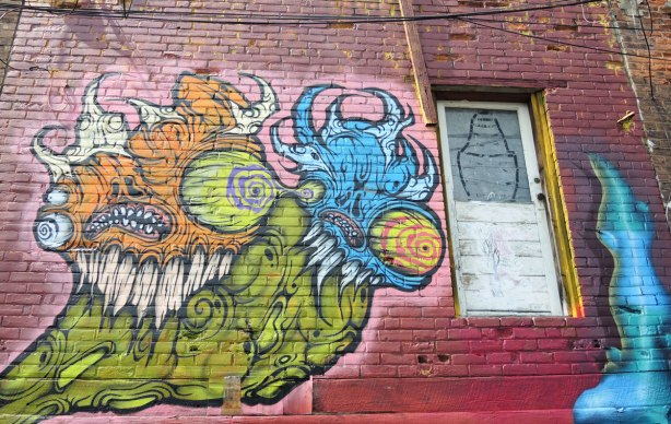 graffiti and street art in Graffiti Alley in Toronto - a very large grominator on the second storey, beside a door that goes nowhere