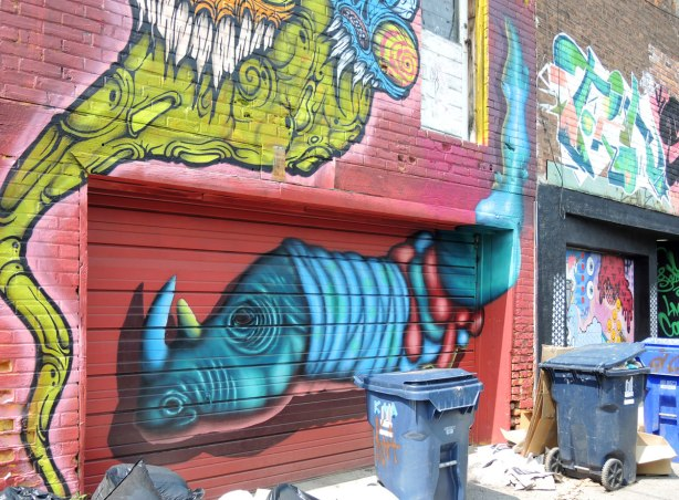 graffiti and street art in Graffiti Alley in Toronto - a large two headed grominator above a garage door, and a birdo creature on the door.