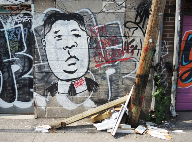graffiti and street art in Graffiti Alley in Toronto - A large white man's face on a garage door, with a pile of broken boards in front of it.  The man is supposed to be Kim Jong of North Korea