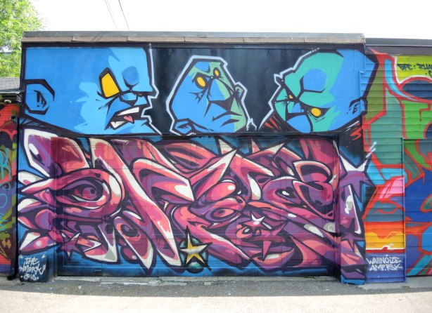 graffiti and street art in Graffiti Alley in Toronto - three large scowling men's heads in blue above a garage door that has swirls in pinks and purples.
