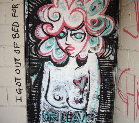 graffiti and street art in Graffiti Alley in Toronto -  the upper part of a topless woman with curly pink and turquoise hair.  Running vertically beside her are the words 'I got out of bed for this'  and below her is the words 'or leave'