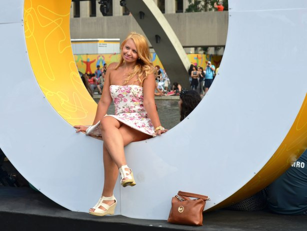 A young blonde woman is posing inside the O of the Toronto sign.