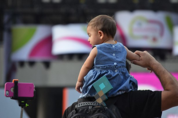 A toddler sits on her father's shoulders.  He is holding onto one of her arms.  She is looking at a pink smartphone being held up by a selfie stick almost to her level.