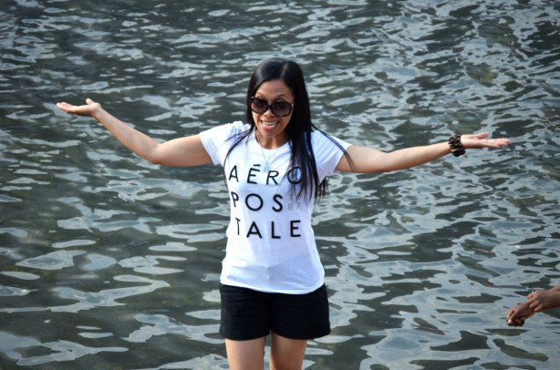 A young woman with long black hair and an Aeropostale T-Shirt stands beside the water with her arms raised to shoulder level.