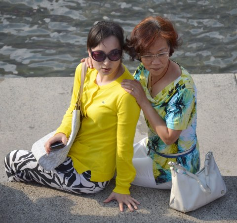 Two Asian women sit on a concrete wall beside water.  They are probably mother and daughter.   They are posing for a photograph.