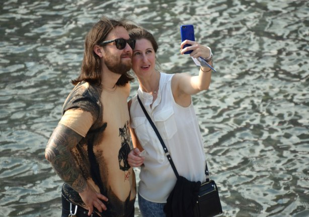 A couple takes a selfie beside water.  He has long hair, a beard and is wearing sunglasses.