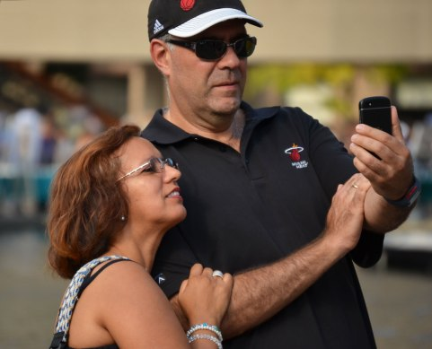A middle aged man and woman are looking at a selfie that they have just taken on a cellphone.