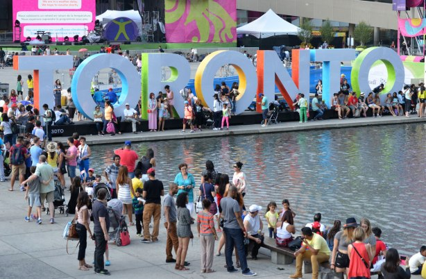 Many people are standing in front of the 3D Toronto sign at Nathan Phillips square.  There are also many people standing around the pool.